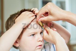 Kind bekommt ein Heftpflaster auf Beule an der Stirn