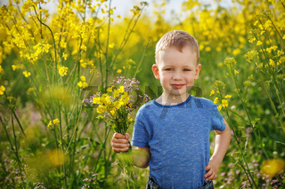 Cute boy with a bouquet of flowers is in the yellow flowering rapeseed field