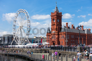 CARDIFF/UK - JULY 7 : View of the Ferris wheel and the Pierhead Building in Cardiff on July 7, 2019. Unidentified people