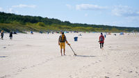 Treasure hunter with metal detector on the beach of Swinoujscie on the Polish Baltic coast