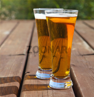 Two glasses of light beer on a table outdoors