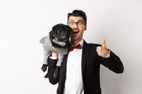 Happy young hipster in suit and glasses, showing thumb-up, holding cute black dog on shoulder, love his pug, standing over white background