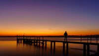 A man silhouette standing on wooden pier lonely at the sea with beautiful sunset. lsunset seascape at a wooden jetty.