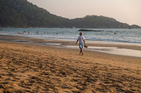 Man walking in waves on beach