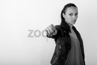 Studio shot of young Asian woman pointing at distance while wearing leather jacket against white background