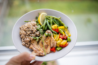 Hand holding a chicken and buckwheat dish with green beans