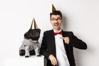 Cheerful man and cute black pug wearing party cones and suits, dog owner celebrating pet birthday, standing over white background