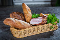 Bread and smoked meat in a braided basket on the table.