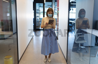 Asian businesswoman wearing face mask standing in corridor using tablet