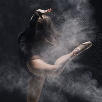 Woman in black body jump with dust cloud profile shot