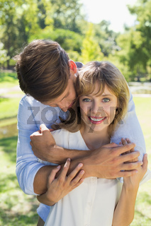 Cute couple hugging in the park with girl smiling at camera
