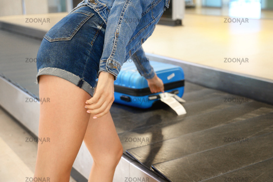 Unrecognizable Woman traveler picking up suitcase from baggage claim in airport terminal.