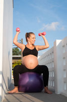 Portrait of pretty pregnant woman exercises with fitball and dumbbells outdoors