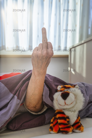 Senior woman in bed shows stink finger