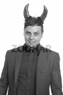 Studio shot of crazy Caucasian businessman wearing devil horns
