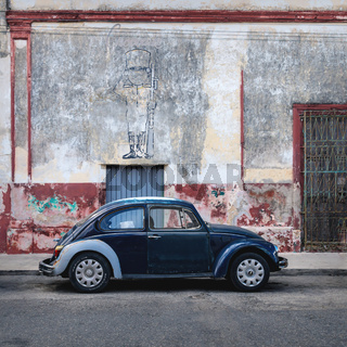 Blue Volkswagen Beetle in the colonial street of Merida, Yucatan, Mexico