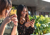 Young millennial Asian friends hanging out outdoors instant messaging on smartphones - Happy smiling