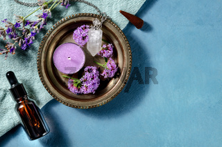 Aromatherapy concept. Essential oil bottle, incense cone, scented candle with verbena and lavender, overhead shot with copy space
