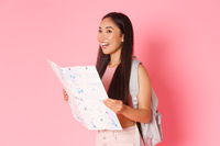 Travelling, lifestyle and tourism concept. Side view of attractive asian girl tourist, traveller with backpack looking at map, explore city, going sightseeing or searching hostel, pink background