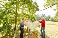 Drei Senioren breiten zusammen eine Decke aus