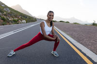 Fit african american woman in sportswear stretching on a coastal road
