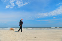 Business man with dog at the beach