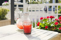 Glass and jar with refreshing drink in garden