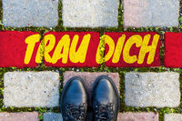 Schoes in front of a red line with the text TRAU DICH