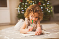 Girl thinking about letter to Santa on floor