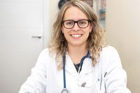 Confident female doctor posing smiling in her office.