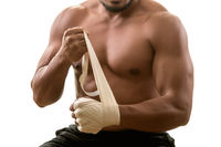Young muscular strong man putting on bandages, isolated on white background. Martial arts, fitness, workout concept