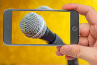 Microphone on smartphone screen. Professional dynamic microphone. Concert microphone for voice recording and sound enhancement. Sound equipment.