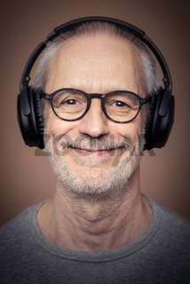 Portrait of adult man with beard wearing stereo headset and glasses.