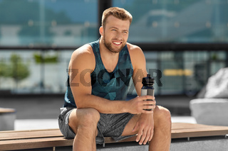 happy sportsman with bottle sitting on city bench