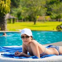 Portrait of a young beautiful woman in white cap and sunglasses lying on a sun lounger on against the background of the pool background