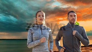 happy couple with earphones running over sea