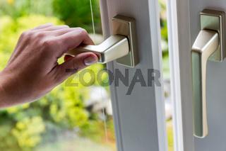 Frau öffnet Fenster zum Lüften