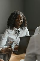 A group of people are joking while sitting at work. Young pretty African American woman smiling to a female employee sitting on against her at the computer