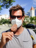 Young guy on summer vacations wearing corona virus protective face mask not beeing able to lick ice cream bar
