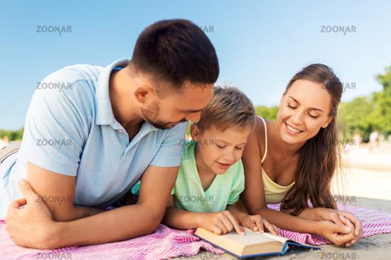 family reading book on summer beach