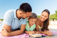 family reading book on summer beach