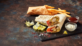 Eastern traditional shawarma and French fries with sauces on slate