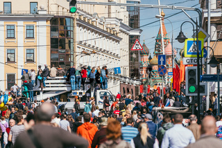 MOSCOW, RUSSIA-MAY 09, 2015: People celebrate Victory Day May 9 in Bol'shoy Moskvoretskiy Most. People climb on white truck to see the parade against the backdrop of the Kremlin . A lot of people with the Ribbons of Saint George