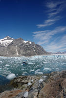 A small boat floats in front of the Knud Rasmussen Glacier in Eastern Greenland..jpg