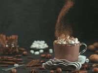 cinnamon powder flying over glass mug with hot chocolate