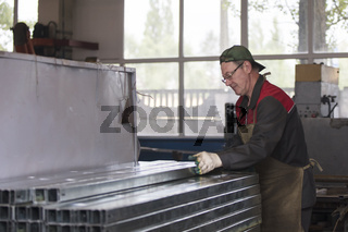 Worker in a workshop with metal ventilation pipes.
