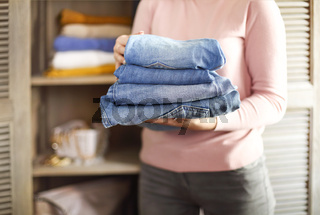 Young shopkeeper woman holding pile of jeans over light background in her hands