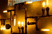 Modern led light made from water pipes. Rustic design, stucco wall with light bulbs and pipes