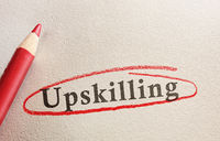 Upskilling text on paper circled in red pencil -- job training concept