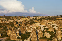 View on evening sunlit Cappadocia valley with cave houses in rocks . Turkey, Goreme.